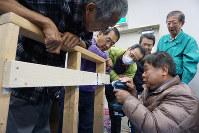 家具を固定する金具の取り付け方を学ぶ、家具固定ボランティア養成講座の受講者たち=愛知県知立市で