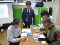 スマホの安全な使用法を教える工藤さん(左から2人目)=毎日メディアカフェで