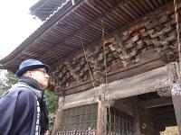 旅人が毒消しの護符を受けた妙法寺を訪れた一之輔さん=濱田元子撮影
