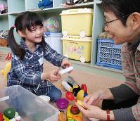 子どもとままごとをして遊ぶ参加者(右)=兵庫県伊丹市千僧1の伊丹市中央公民館で、山本未来撮影