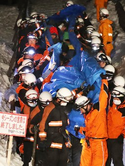 High school students, who were rescued after being hit by an avalanche at Nasuonsen Family Ski Resort in Nasu, Tochigi Prefecture, come down the mountain on March 27, 2017, covered by blue sheets for privacy reasons. (Mainichi)