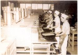 昭和30年代の即席カレー作り。大きなフライパンを並べ、職人が手作業でいためていた=オリエンタル提供