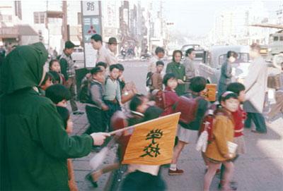 東京の目抜き通りのひとつ、上野広小路交差点で黒門小学校の子どもたちを誘導する緑のおばさん=東京都台東区の上野広小路で1959年12月撮影