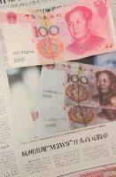 新たな偽札について報じる中国紙「新京報」(上は本物の100元札)=2014年5月25日、北京市内で工藤哲撮影