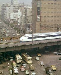 東海道新幹線は開業前の試運転まで国民の注目の的だった。東京・新橋駅付近を試運転する車両を駅のホームで大勢の乗客が見物している=1964年8月