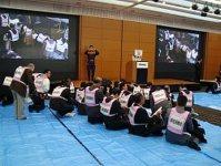 帰宅困難者を受け入れる訓練でブルーシートに座って待機する参加者=東京都渋谷区で2014年12月5日、渋谷駅周辺帰宅困難者対策協議会提供