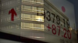 株価ボードに映り込むビル=東京都中央区で関口純撮影