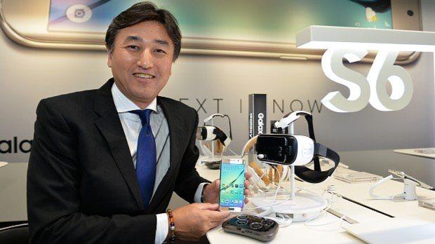 新端末「ギャラクシーS6」を手にする堤浩幸最高執行責任者=関口純撮影