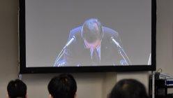 シャープの株主総会で頭を下げる高橋興三社長を映すモニター画面=大阪市西区で6月23日、川平愛撮影