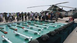 中国軍が公開した軍用ヘリコプター(後方)と搭載用の砲弾