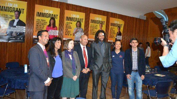 ポスターの前で記念撮影をするタジさん(左から4人目)ら参加者たち