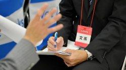 メモとペンを手に企業のPRを熱心に聞く就活生=関口純撮影