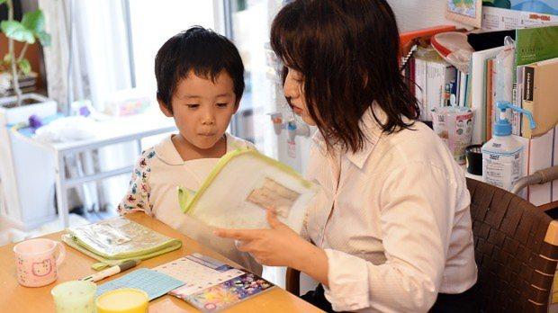 働きながら子供を育てる女性。保育園の連絡帳を準備中=埼玉県鶴ヶ島市で2015年8月4日、関口純撮影