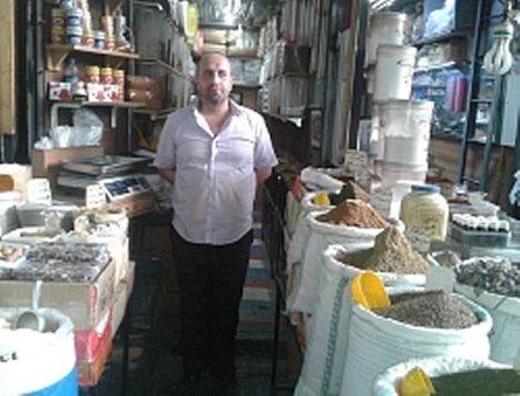 シリアの首都ダマスカス旧市街で、ハーブ店を営むマジャド・アーキさん。さまざまな乾燥ハーブが売られている=2015年8月31日、フアード・アリ撮影
