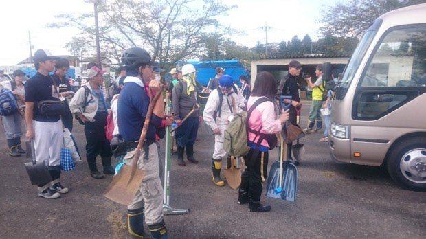 スコップやブラシを手にバスに乗り込むボランティア=茨城県常総市で9月15日午前9時40分、今沢真撮影