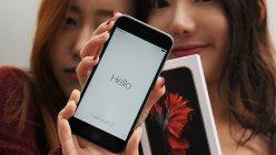 手に入れた「iPhone 6s Plus」を手に喜ぶ女性=福岡市中央区で2015年9月25日、山下恭二撮影