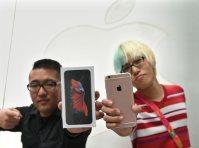 一番乗りで購入したiPhone 6s Plusを手にする人たち=大阪市中央区で2015年9月25日