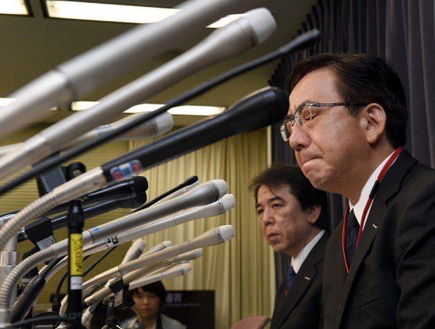 厳しい表情で記者会見する堺正光・旭化成建材常務(右)=国交省で2015年10月22日