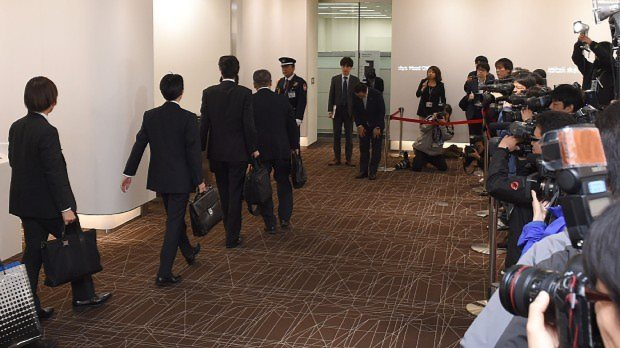大勢の報道陣が集まる中、旭化成建材本社に立入検査に入る国交省の職員ら=東京都千代田区で2015年11月2日