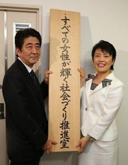 看板をかける安倍晋三首相(左)と有村治子女性活躍担当相(当時)=東京都千代田区の内閣府で2014年10月