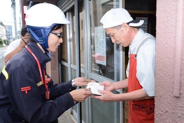 マイナンバーの通知カードを配達する郵便局員(左)=2015年11月9日、宮原健太撮影