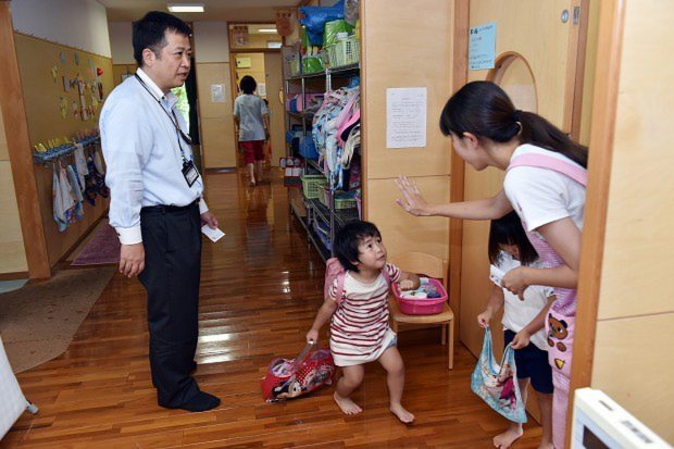 父親のお迎えに喜び、先生とバイバイをする子供=埼玉県鶴ヶ島市のかこのこ保育園で、関口純撮影