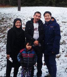 ドイツ南部メスシュテッテンの施設前で、アリさん一家と写る坂口裕彦記者=21日