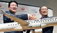 MRJの模型を前に笑顔で握手を交わす植木義晴・日本航空社長(左)と江川豪雄・三菱航空機会長=東京都品川区で2014年8月28日、小関勉撮影