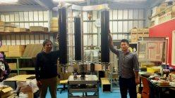 垂直軸型マグナス風力発電機のプロトタイプとチャレナジーの清水敦史社長(左)と小山晋吾取締役