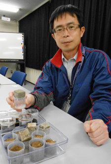 実験で使ったブロック片を手にする山西弘城教授=東大阪市小若江3の近畿大学原子力研究所で、関野正撮影