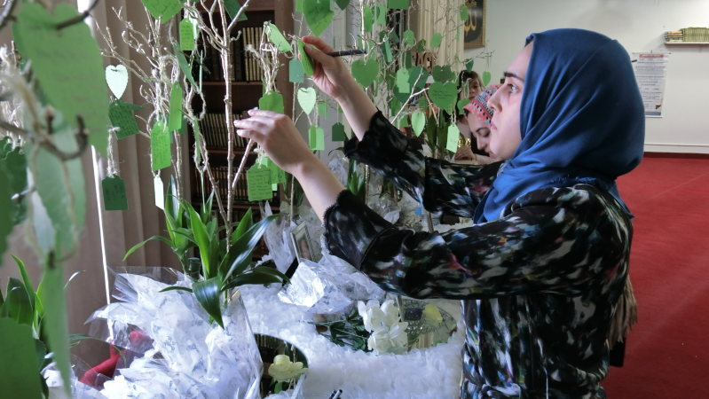 米カリフォルニア州の福祉施設で起きた銃乱射事件の犠牲者に向け、メッセージを捧げるイスラム教徒の女性ら=2015年12月6日、長野宏美撮影