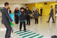 左折してきた「トラック」役の警察官に合図し、模擬交差点を渡る高齢者ら=大阪府忠岡町総合福祉センターで、千脇康平撮影