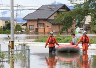 A man is rescued by boat in the Miyagi Prefecture city of Osaki after the Shibui River burst its banks, on the morning of Sept. 11, 2015. (Mainichi)