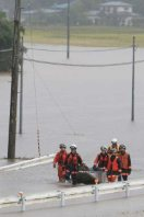 Rescuers walk next to a boat, checking if anyone needs help, on a flooded road in Osaki, Miyagi Prefecture, on Sept. 11, 2015. (Mainichi)