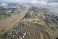 In this photo taken from a Mainichi helicopter on Sept. 11, 2015, the Ibaraki Prefecture city of Joso is pictured after the Kinugawa River, seen at left, overflowed and inundated the area. (Mainichi)