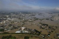 The Mitsukaido district of Joso, Ibaraki Prefecture, lies inundated after the Kinugawa River overflowed in torrential rain, in this photo taken from a Mainichi helicopter on Sept. 11, 2015. Pictured at the bottom of the photo is the Kokai River. (Mainichi)