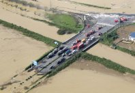 Fire trucks and Self-Defense Forces vehicles are seen gathered on a strip of road that avoided flooding in Joso, Ibaraki Prefecture on Sept. 11, 2015. (Mainichi)