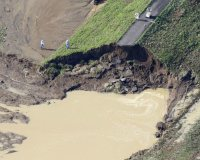A large hole is seen in a dike a day after the Kinugawa River burst its banks in Joso, Ibaraki Prefecture on Sept. 11, 2015. (Mainichi)