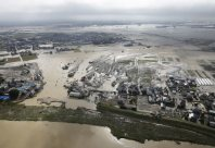 The Ibaraki Prefecture city of Joso is seen on the morning of Sept. 11, 2015, a day after the Kinugawa River, pictured at the bottom, burst through an embankment, in this photo taken from a Mainichi helicopter. (Mainichi)