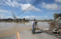 A road is completely cut off after water burst through a river levee, right background, in this photo taken on Sept. 11, 2015. (Mainichi)