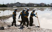 Police search the flooded area near where a river levee was damaged, on Sept. 11, 2015. (Mainichi)
