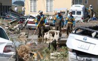 Police search among vehicles that were swept away by floodwaters in Joso, Ibaraki Prefecture, on Sept. 11, 2015. (Mainichi)