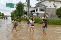 People emerge from a regional exchange center that served as a shelter, background right, in Joso, Ibaraki Prefecture, on Sept. 11, 2015. (Mainichi)
