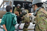 Two people and a dog are seen before getting into a Self-Defense Forces helicopter, on the roof of the Apita shopping complex in Joso, Ibaraki Prefecture, on Sept. 11, 2015. (Mainichi)