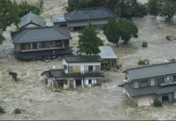 People seek help from the second floors of homes that were hit by flooding in Joso, Ibaraki Prefecture, on the afternoon of Sept 10, 2015. (Mainichi)