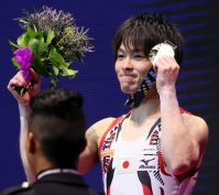 Kohei Uchimura holds his gold medal on the winners' podium after his sixth career gold medal for individual all-around gymnastics at the World Gymnastics Championships in Glasgow, Scotland, on Oct. 30, 2015. (Mainichi)