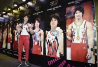 Kohei Uchimura poses in front of pictures of himself and other past champions after winning his sixth career gold medal at the World Gymnastics Championships in Glasgow, Scotland, on Oct. 30, 2015. (Pool photo)