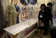 ひつぎに眠る故人に着せるアトリエ・エムのラストドレス。硬直した体に着せやすい作りが特徴。和装もあるが、ドレスが人気という=東京都江東区の東京ビッグサイトで2015年12月8日、中村美奈子撮影