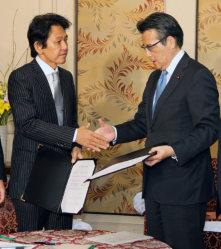 合意書を交わし握手する民主党の岡田代表(右)と維新の党の松野代表=国会内で11日、山本晋撮影