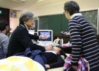 子どもの首にエコー検査器を当てて、保護者に説明する野宗義博医師(左)=塩谷町大宮の大宮コミュニティーセンターで